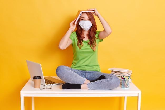 Рыжая девушка в медицинской маске сидит со скрещенными ногами на столе, в джинсах и зеленой футболке, устала от долгого нашего дистанционного обучения Бесплатные Фотографии