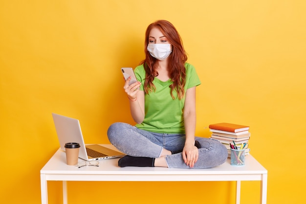 Red haired high school girl sit on table in lotus pose, uses smart phone, chatting with friends while having break, wearing jeans and green t shirt, medical mask isolated over yellow background. Free Photo