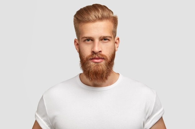 Red haired serious young man blogger looks confidently Free Photo