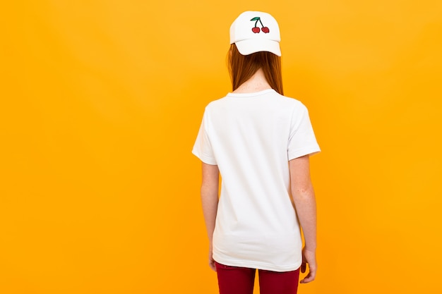 Red-haired teenager stands with his back  on a yellow isolated Premium Photo