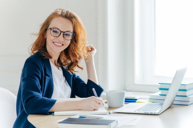 Рыжая женщина анализирует данные и составляет бухгалтерский отчет Premium Фотографии