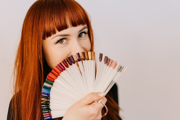 Red-haired woman holds samples of a gel-varnish in her hand in the form of a semicircle on white. Premium Photo