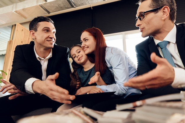 Red-haired woman hugs girl sitting between two adult men Premium Photo