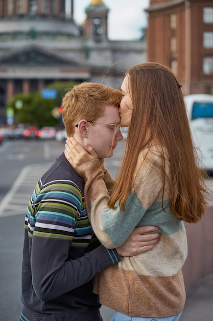 Red-haired woman kisses a man on the top of her head, a woman with long dark thick hair in sweater Premium Photo