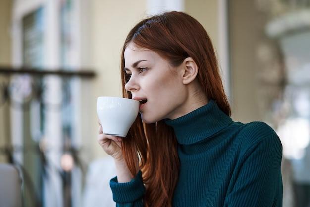 Рыжая женщина в уличном кафе с чашкой кофе Premium Фотографии