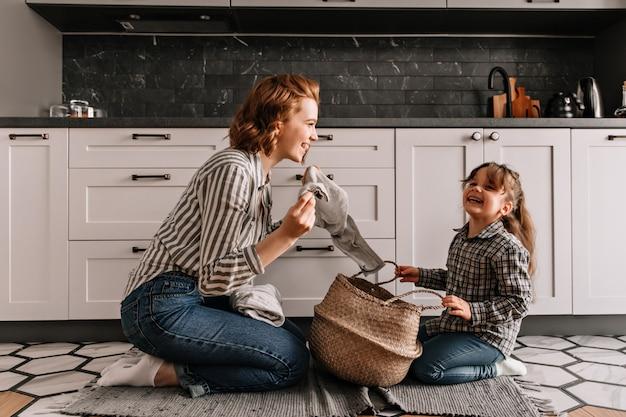Рыжеволосая женщина шутит дочери и достает грязную одежду из корзины. Бесплатные Фотографии