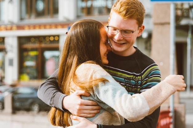 A red-haired young man embraces young woman with long dark hair, they laugh Premium Photo
