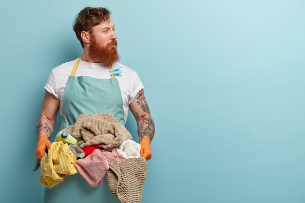 Рыжий молодой человек, забитый домашними делами, держит таз с кучей белья, носит повседневную футболку и фартук, смотрит в сторону, изолирован за синей стеной, у него задумчивый вид, сосредоточенный Бесплатные Фотографии
