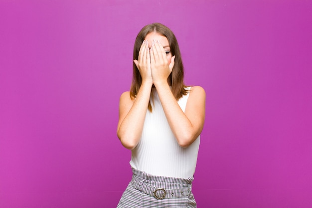 Red head pretty woman covering face with hands, peeking between fingers with surprised expression and looking to the side against purple wall Premium Photo