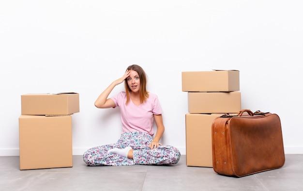 赤い頭のきれいな女性が幸せで、驚いて、驚いて、笑顔で、新しい家で驚くほど信じられないほどの良いニュースを実現 Premium写真