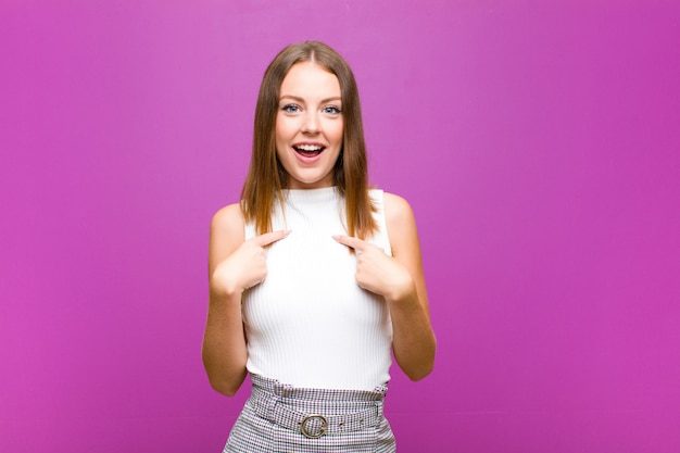 Red head woman feeling happy, surprised and proud, pointing to self with an excited, amazed look on purple wall Premium Photo