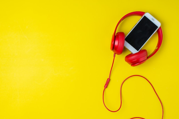 Red headphone and smartphone music concept background on yellow Premium Photo