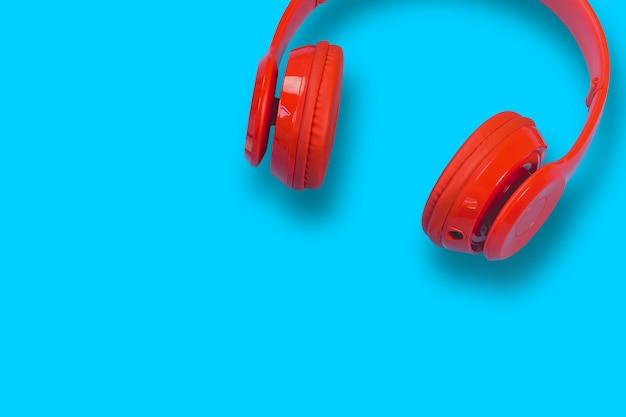 Red headphones on blue pastel table Premium Photo
