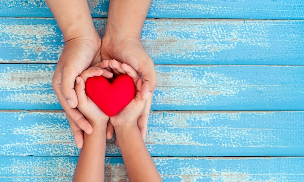 Red heart in child kid and mother hands on old blue wooden table Premium Photo