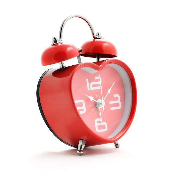 白い背景の上のベルと赤いハート時計 Premium写真