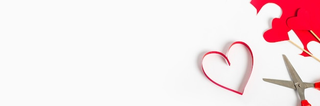Red heart cut from paper, scissors and colored cardboard on a light white background. composition valentine's day. banner. flat lay, top view. Premium Photo