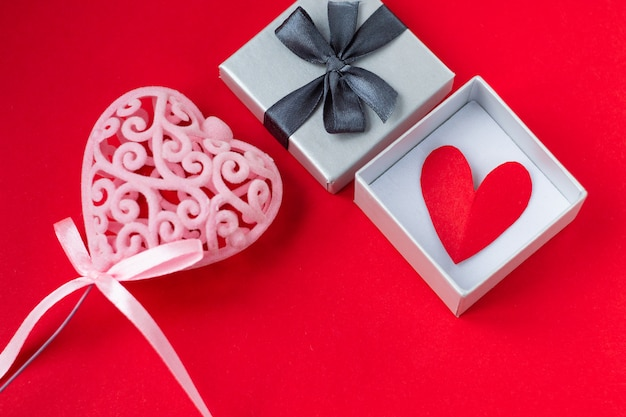Red heart in gift box on red background Premium Photo