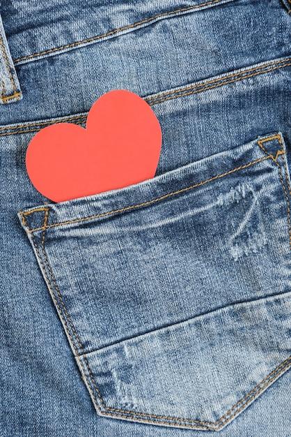Красное сердце в кармане джинсов. день святого валентина концепция Premium Фотографии