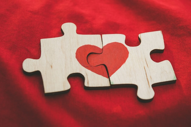 Red heart is drawn on the pieces of the wooden puzzle lying next to each other on red background. Premium Photo