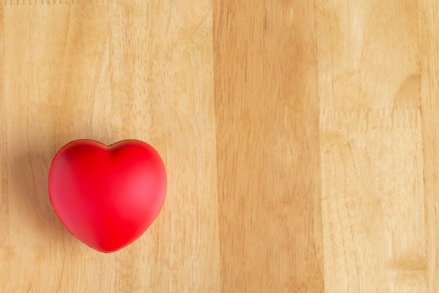 Red heart is placed on wooden floor Premium Photo