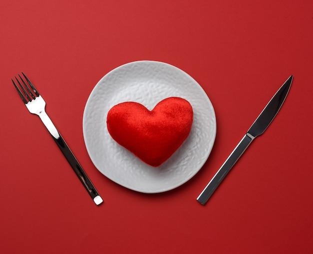 Красное сердце лежит в белой керамической тарелке на красном фоне Premium Фотографии