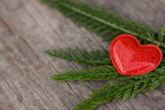 Red heart lies on a wooden background with green leaves Premium Photo