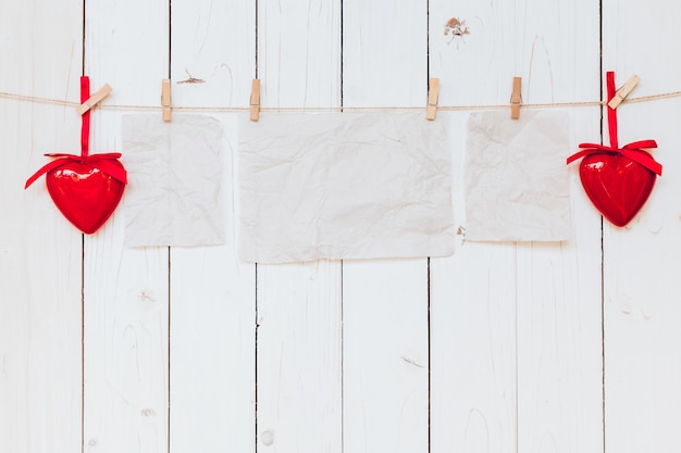 Red heart and old paper blank hanging at clothesline on wood white background with space. valentine day. Premium Photo