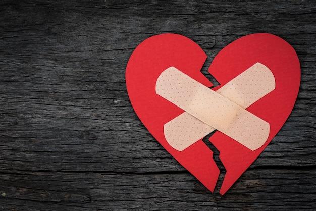 Red heart paper on wooden background. heart broken, love concept. Premium Photo
