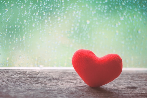 Red heart on rainy day window background in vintage color tone Premium Photo