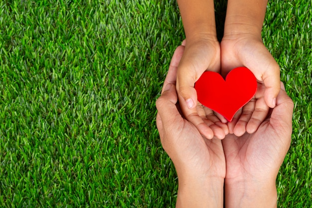 Red heart shape in family member's hands holding Free Photo