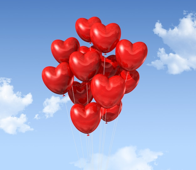 Red heart shaped balloons floating in the sky Premium Photo