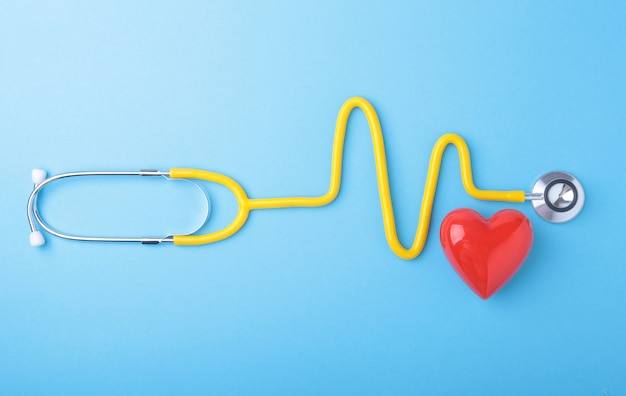 Red heart and a stethoscope on blue background Premium Photo