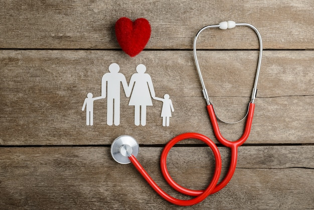 Red heart, stethoscope and paper chain family on wooden table Premium Photo