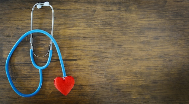 Red heart on stethoscope on wooden background Premium Photo