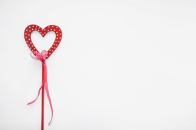 Red heart on stick with ribbon Free Photo