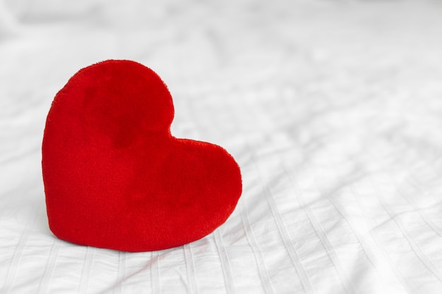 Red heart on white bed Premium Photo