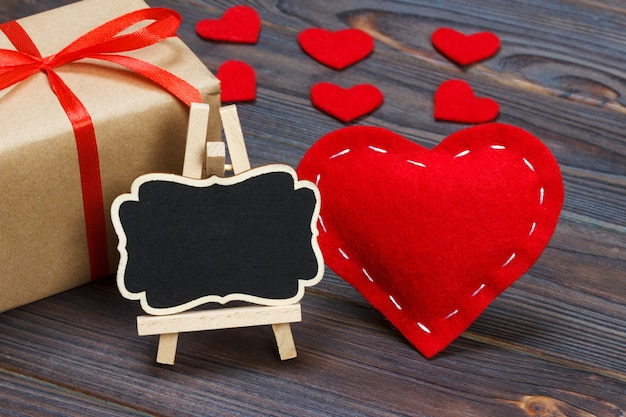 A red heart with black board and small hearts. Premium Photo