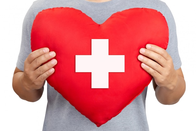 Red heart with cross sign in male hand, close-up.international red cross day Premium Photo