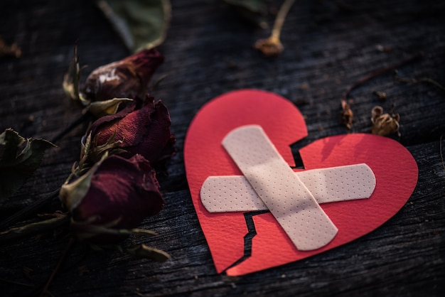 Red heart with dried red rose on wooden background. heart broken concept Premium Photo