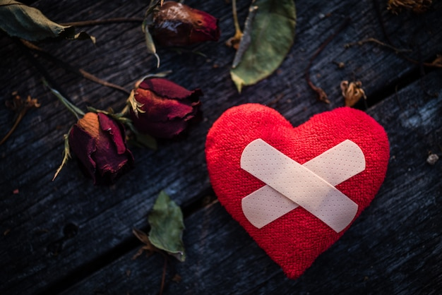 Red heart with dried red rose on wooden background. heart broken, love and valentines. Premium Photo