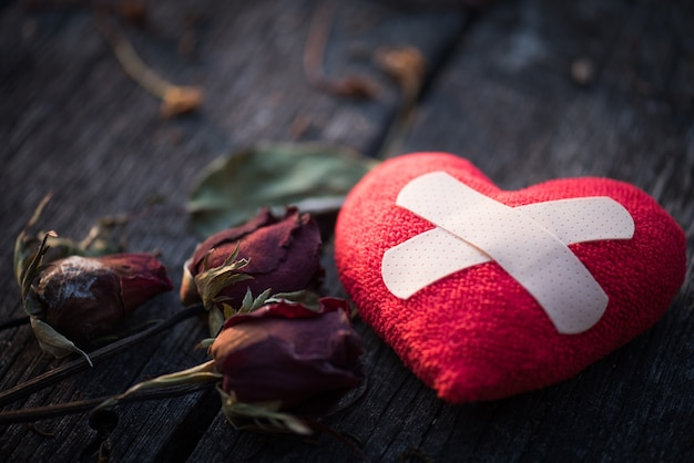 Red heart with dried red rose on wooden background. Premium Photo