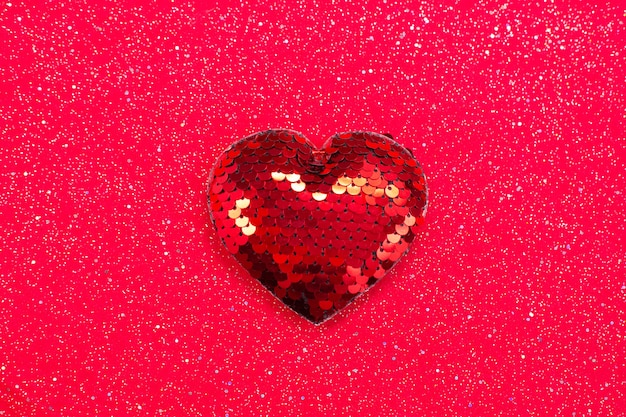 Red heart with sequins on red fabric. Premium Photo
