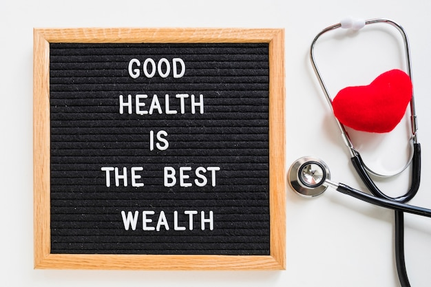Red heart with stethoscope and notice board with good health message on white background Free Photo