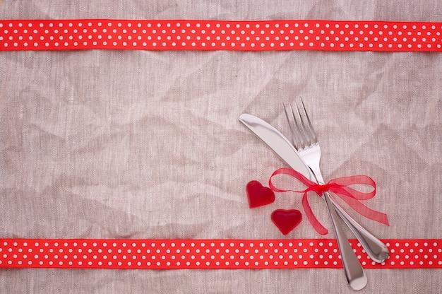 Красные сердечки и столовые приборы на холщовой скатерти Premium Фотографии