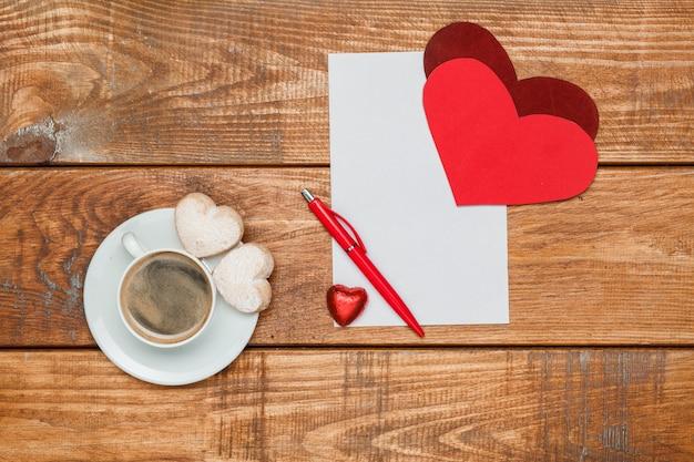 I cuori rossi e il foglio di carta bianco e la penna su fondo di legno con una tazza di caffè Foto Gratuite