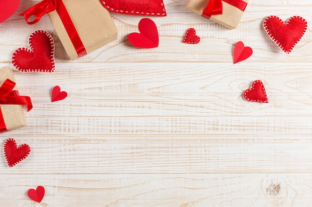 Red hearts and craft gifts on white wooden background Premium Photo