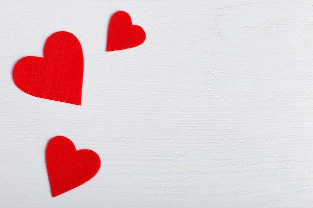 Red hearts of different sizes on a white background Premium Photo