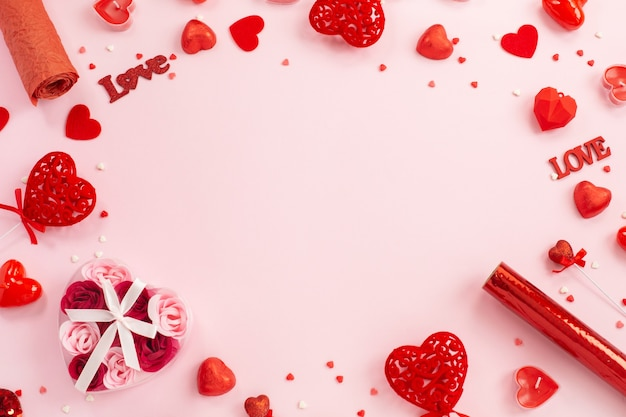 Red hearts, gifts and candles on a festive pink. Premium Photo