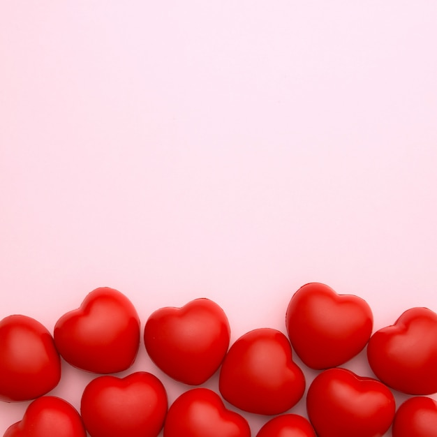 Red hearts on pink background with copy space for valentine's day. love concept. minimal style. Premium Photo
