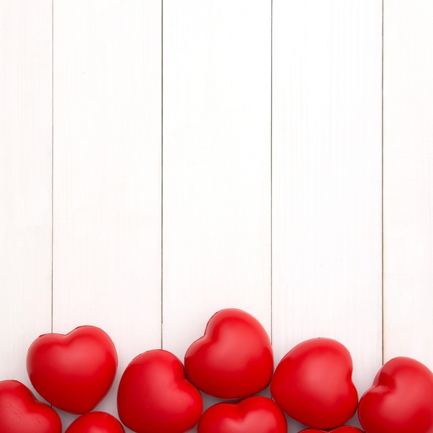 Red hearts on white wooden background with copy space for valentine's day. love concept. minimal style. Premium Photo